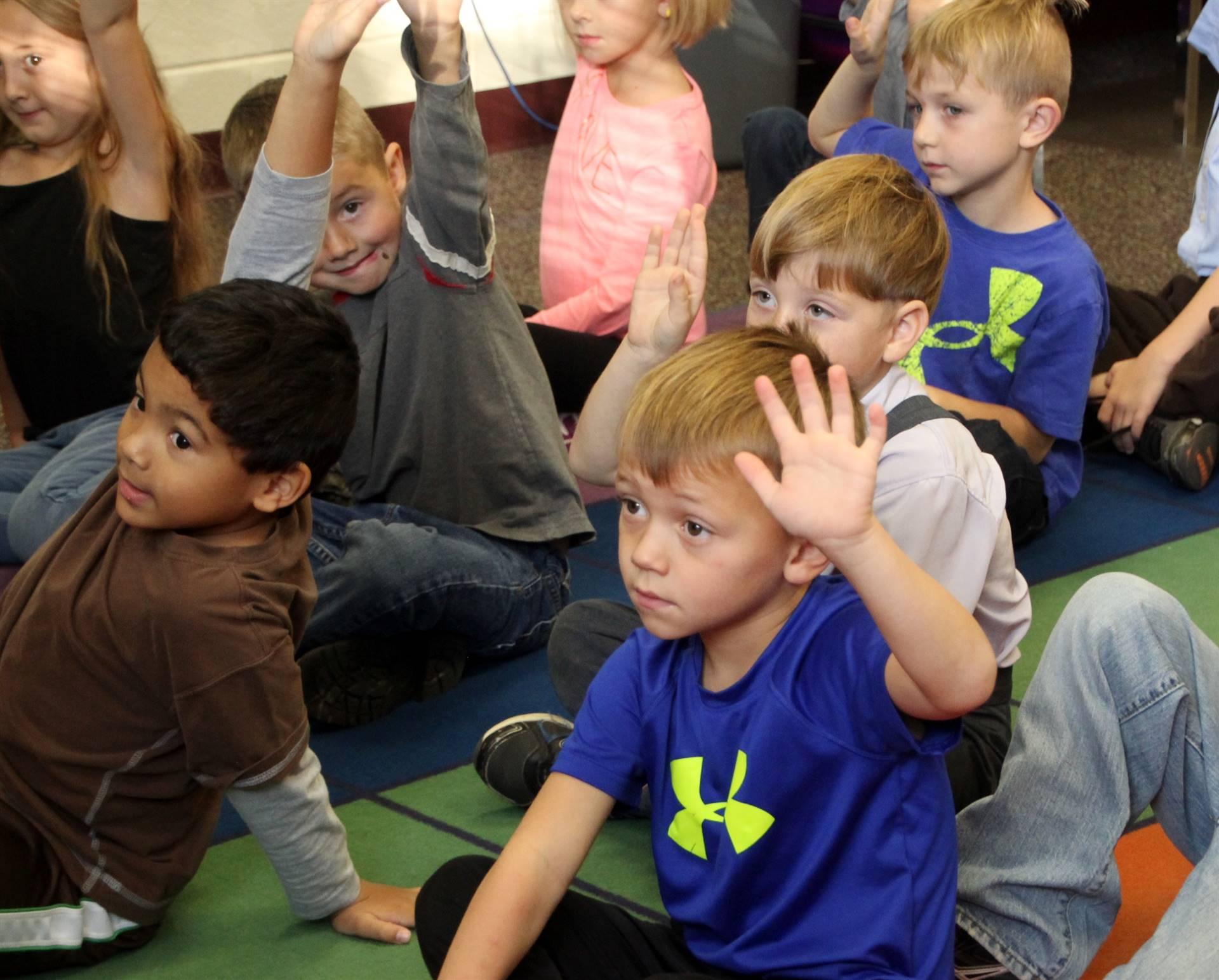 kindergarten kids raising hand